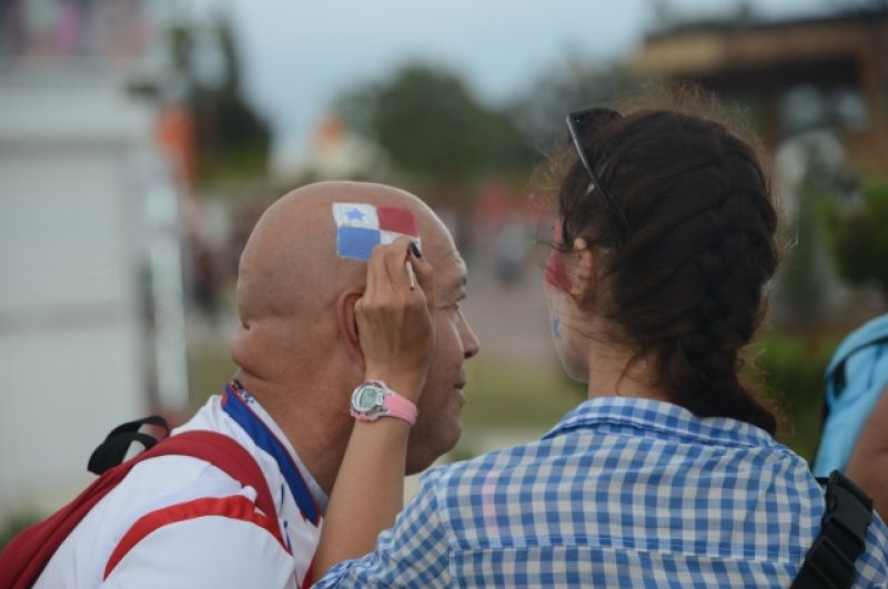 Шведскому болельщику наносят рисунок флага прямо на голову.