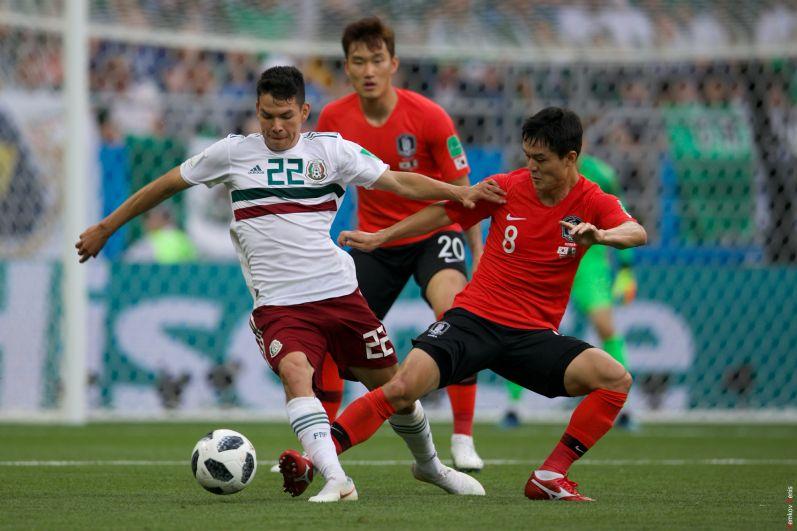 Мексиканский нападающий Марко Фабиан выбивает мяч у защитника сборной Кореи Е Хан Ко.