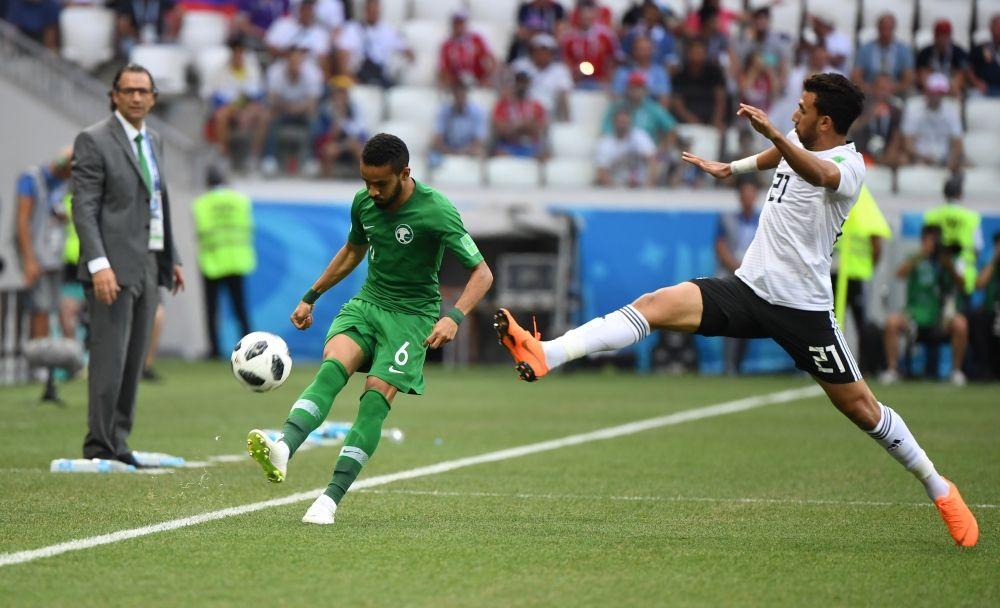 Игрок египетской сборной Махмуд Хасан и Мохаммед Аль-Брейк из сборной Саудовской Аравии борются за мяч в первые минуты матча.