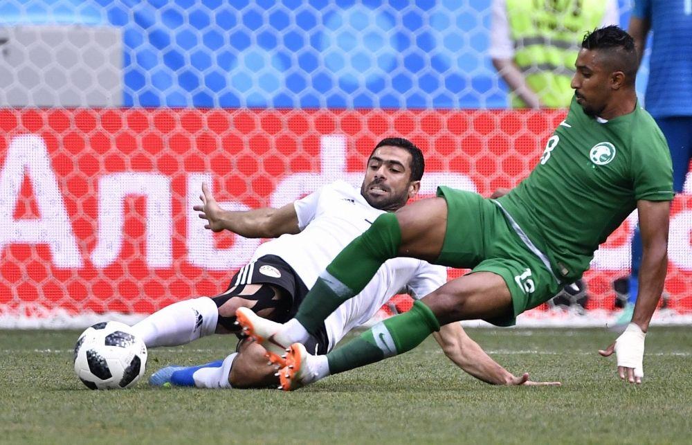 Ахмед Фатхи из египетской сборной не дает противнику Салему Аль-Досари завладеть мячом.