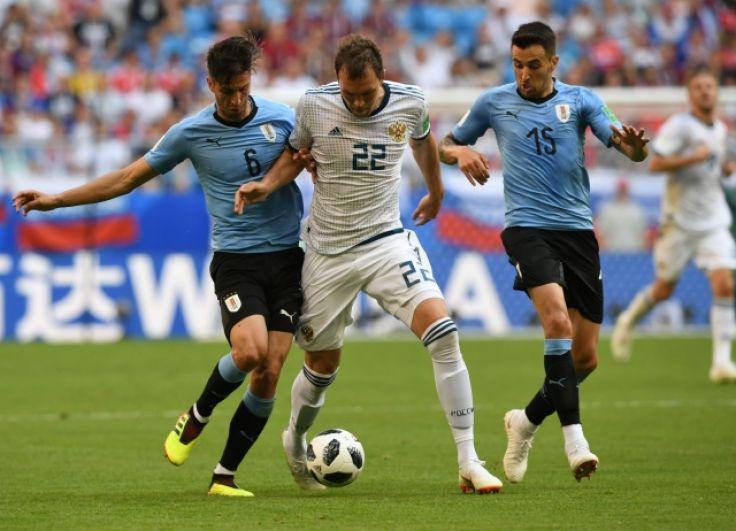 Уругвайцы сразу пытались прессинговать российских игроков. На фото - Артем Дзюба между двумя соперниками.