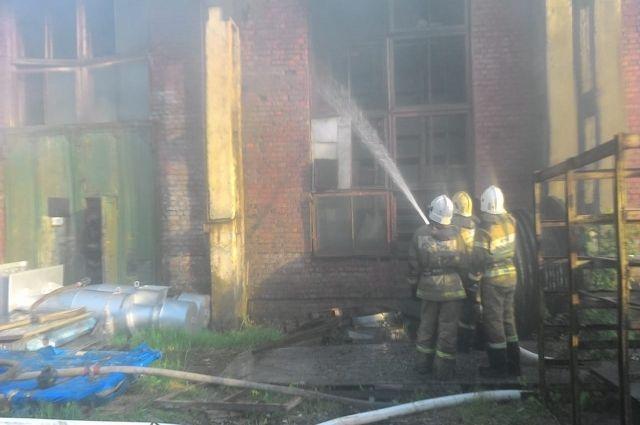 Пожарные работают в горящем цеху.
