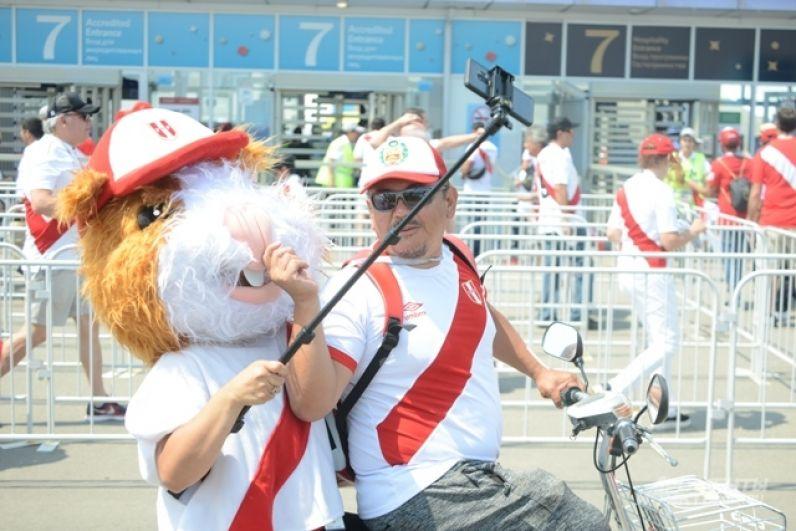 Аниматор фотографируется с фанатом сборной Перу на велосипеде при помощи селфи-палки.