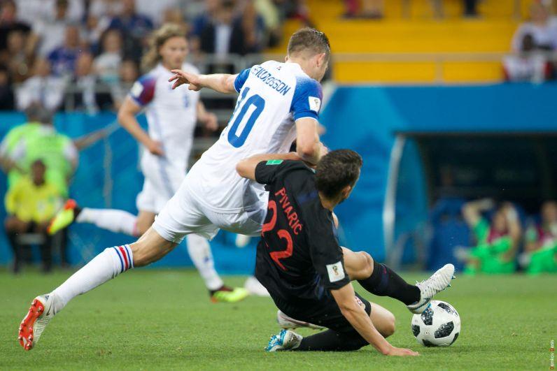 Хавбек и автор единственного гола сборной Исландии Гильфи Сигурдссон роняет Пиварича.