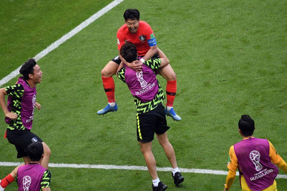 Сон Хын Мин, забивший второй гол, в восторге прыгает на плечи товарищу по команде.