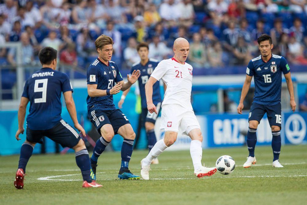 Японцы окружили польского полузащитника Рафала Курзава.