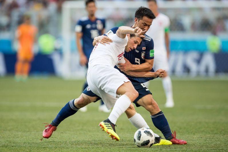 Полузащитник Гжегош Крыховяк и нападающий Синдзи Окадзаки борются за владение мячом.