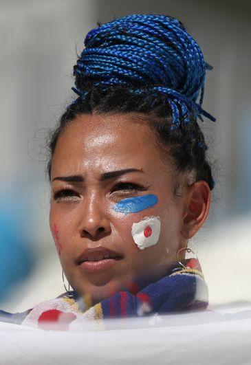 Японка с цветными африканскими косичками, убранными в пучок и флагом своей страны на щеке.