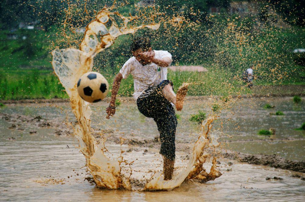 Мужчина играет в футбол во время праздника, который знаменует начало посадки риса в сезон муссонов в Лалитпуре, Непал.