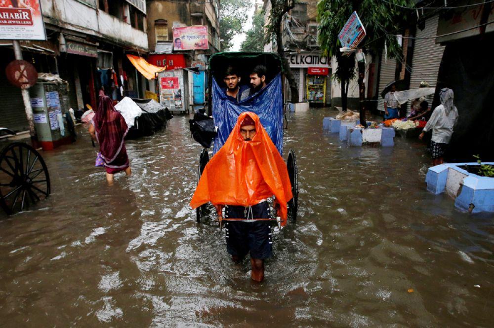 Рикша перевозит пассажиров по улице после сильного дождя в Калькутте, Индия.