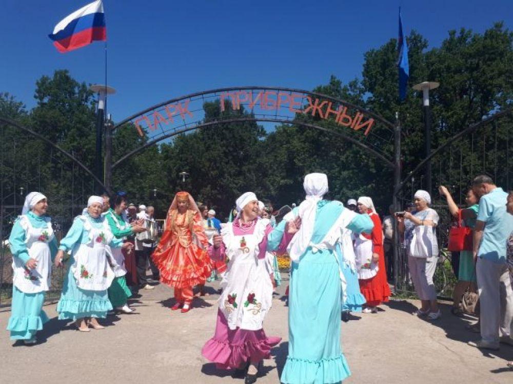 В ожидании приезда почетных гостей у центрального входа девушки поют и танцуют.
