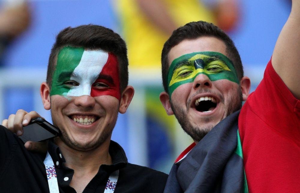 Болельщики обеих сборных с раскрашенными в цвета национальных флагов лицами.