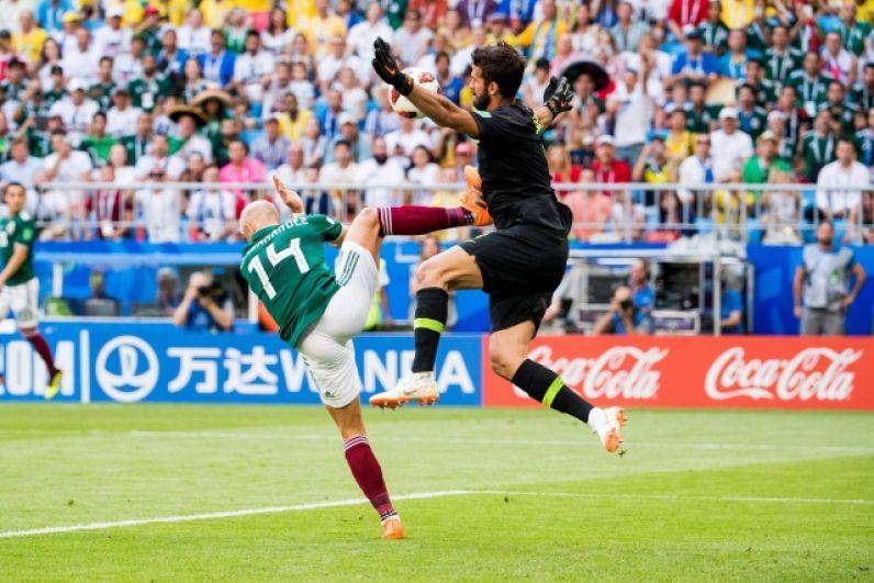 Голкипер Алиссон в жесткой борьбе за мяч.
