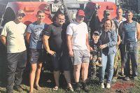 Татьяна с внуком, сыновьями (слева от неё) и механизаторами своего хозяйства.