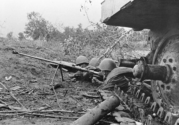 Гвардейцы-бронебойщики отражают танковую атаку врага, лежа рядом с подбитым танком.