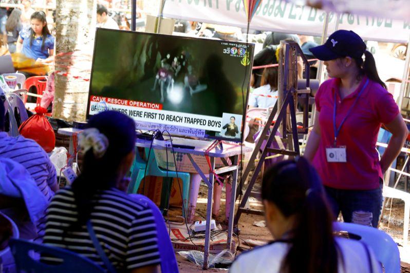 Члены семей смотрят новостную телетрансляцию с места событий.