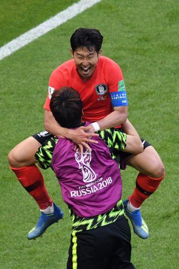 Нападающий сборной Южной Кореи Сон Хын Мин празднует свой гол сборной Германии, забравшись на руки к товарищу.