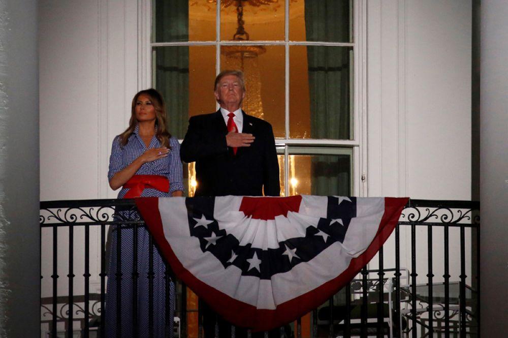 Президент Дональд Трамп и первая леди Мелания Трамп стоят на балконе Белого дома перед началом праздничного салюта.