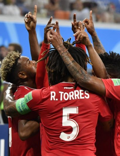 Игроки сборной Панамы, празднуя гол, обнимаются и поднимают вверх руку с вытянутым пальцем.