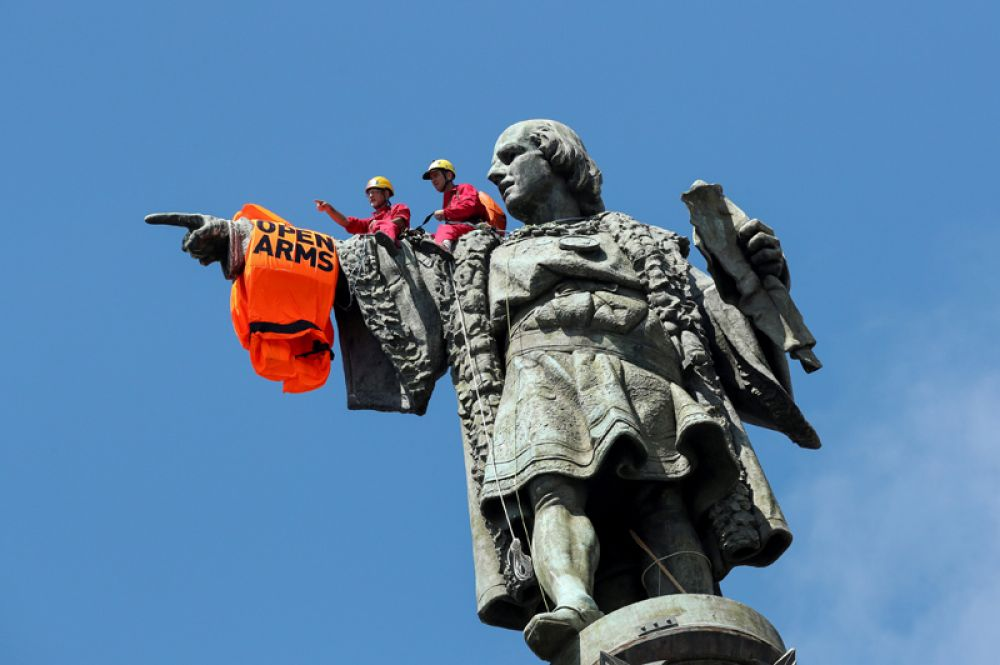 Активисты испанской благотворительной организации Proactiva Open Arms повесили на статую Христофора Колумба спасательный жилет после того, как корабль с мигрантами прибыл в порт Барселоны, Испания.