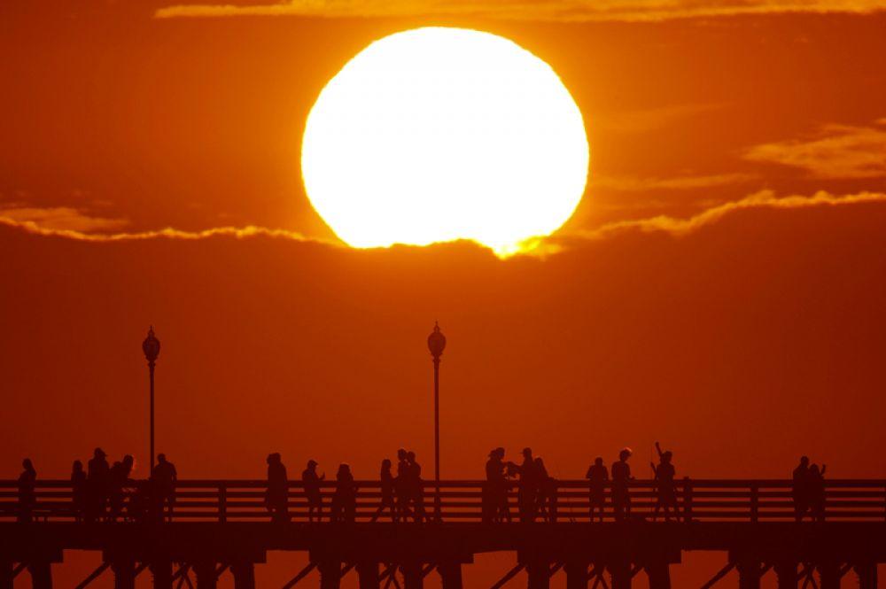 Горожане прогуливаются вдоль океанского пирса в Оушенсайд, Калифорния, США.