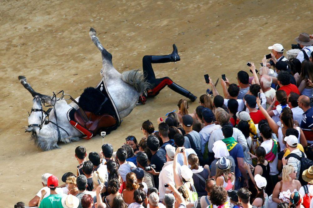 Карабинер падает с лошади во время традиционных скачек «Сиенское Палио», Италия.