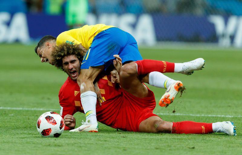 Маруан Фелайни из Бельгии (в красном) и Коутиньо борются за мяч.