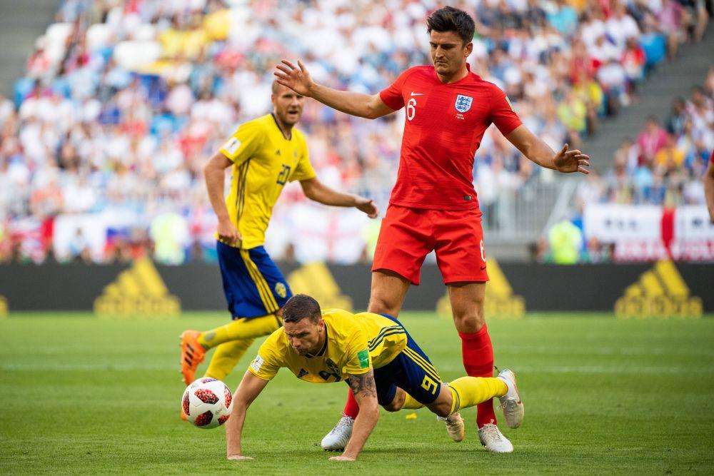 Маркус Берг из Швеции упал, борясь за мяч с Гарри Магуайром.