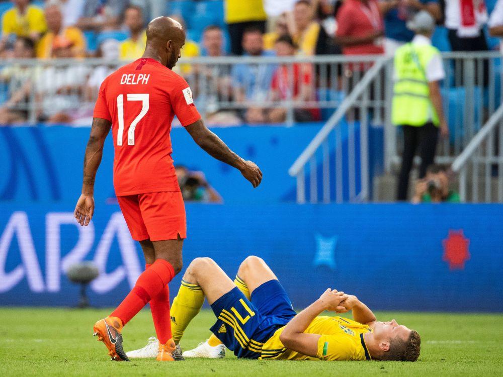 Фабиан Дельф из Англии идет подать руку раздавленному Виктору Клессону из Швеции после матча.