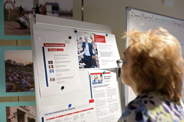 Посетитель у информационного стенда в предвыборном штабе Сергея Собянина.