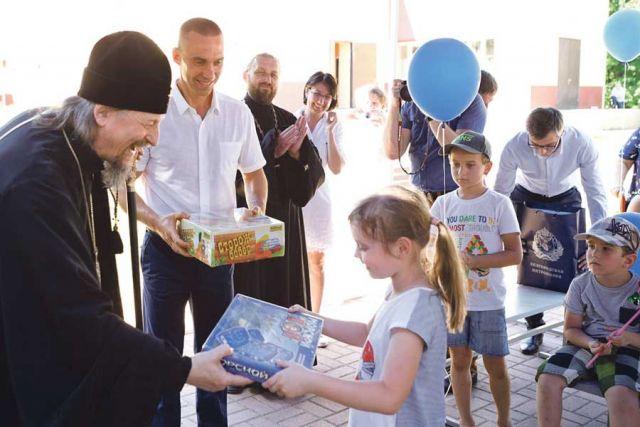 Митрополит Иоанн и Сергей Фуглаев вручают подарки детям из лагеря «Парус мечты».