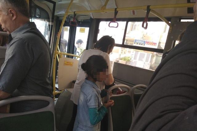 Девочка в автобусе просит милостыню.