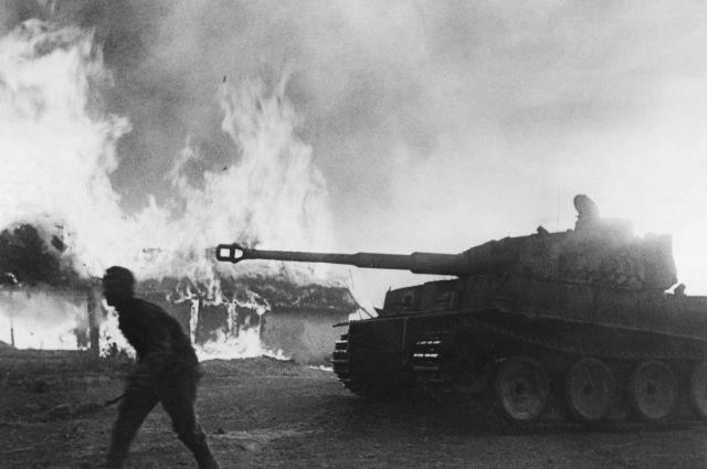 Немецкий танк Pz. Kpfw. VI «Тигр» на фоне горящих домов на Курской дуге.