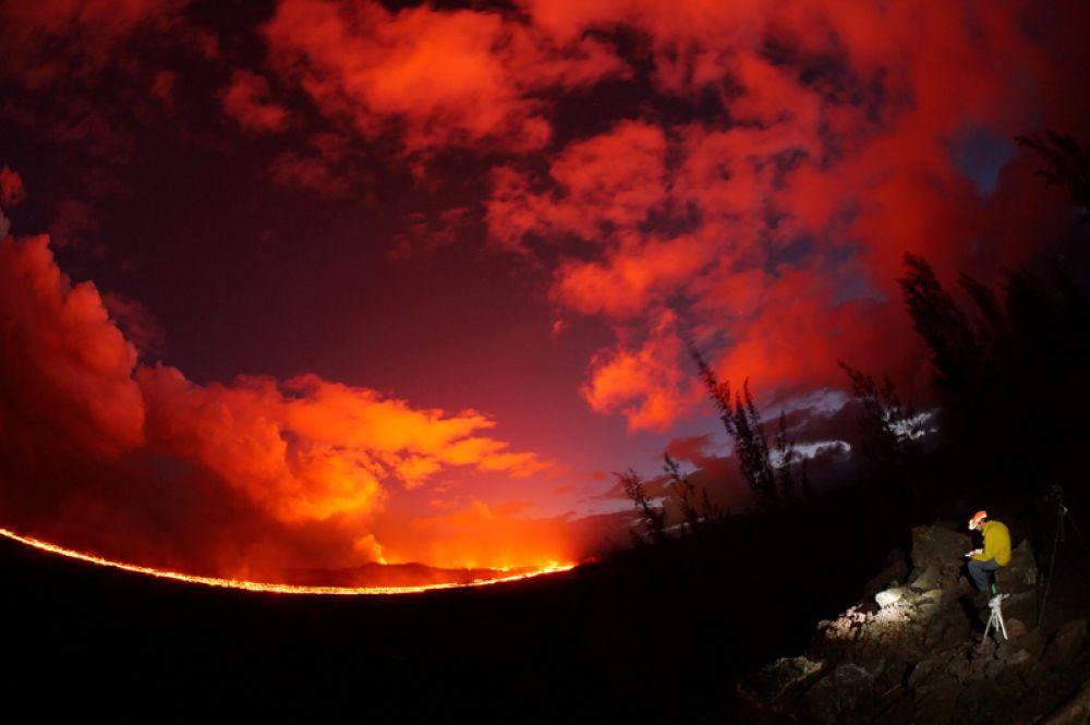 Сотрудник Геологической службы США ведет наблюдения за потоком лавы во время извержения вулкана Килауэа на Гавайях.