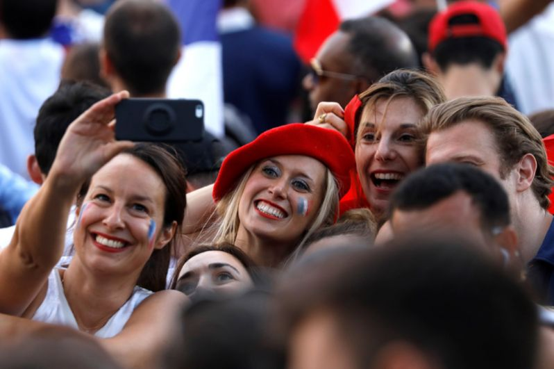 Французы празднуют победу национальной сборной перед Триумфальной аркой на Елисейских полях в Париже.