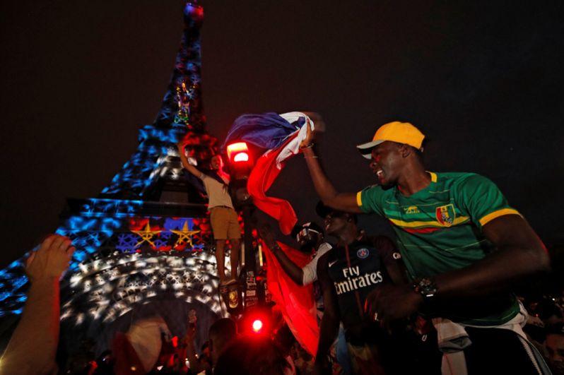 Французы празднуют победу национальной сборной возле Эйфелевой башни в Париже.