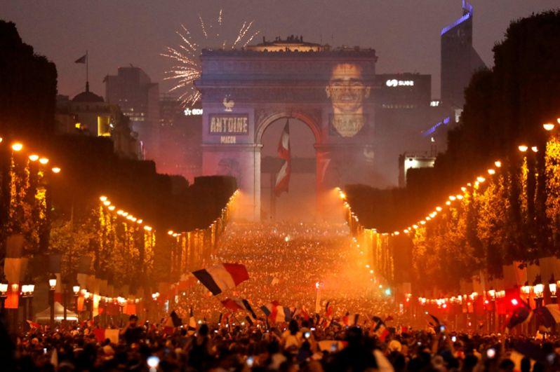 Портрет игрока сборной Франции Антуана Гризманна на Триумфальной арке в Париже после того, как Франция выиграла финал чемпионата мира по футболу.