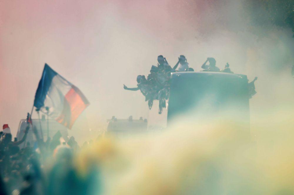 Болельщики встречают национальную сборную на Елисейских полях в Париже.