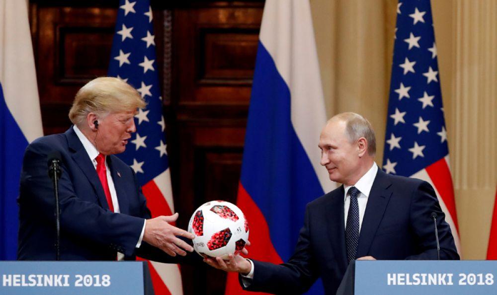 Дональд Трамп получает в подарок от Владимира Путина футбольный мяч во время совместной пресс-конференции после встречи глав государств в Хельсинки, Финляндия.