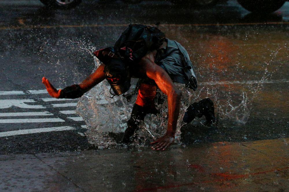 Человек падает в лужу на Таймс-сквер во время сильного ливня в Нью-Йорке, США.