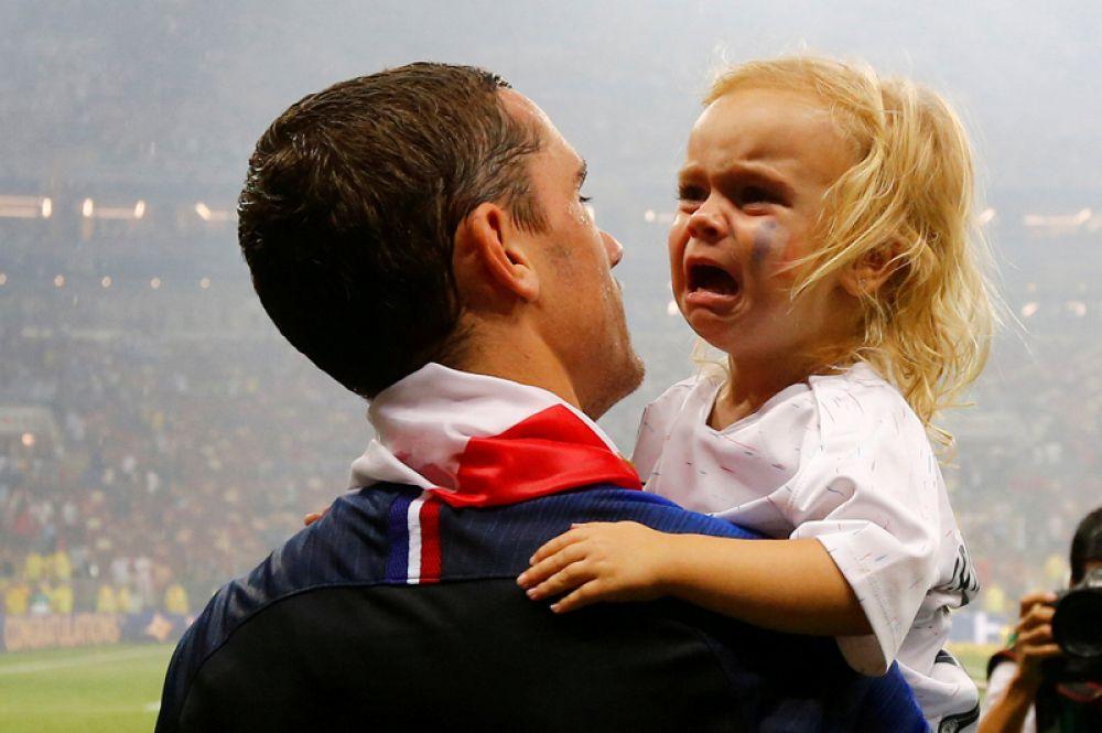 Французский футболист Антуан Гризманн с дочерью после победы на чемпионате мира.