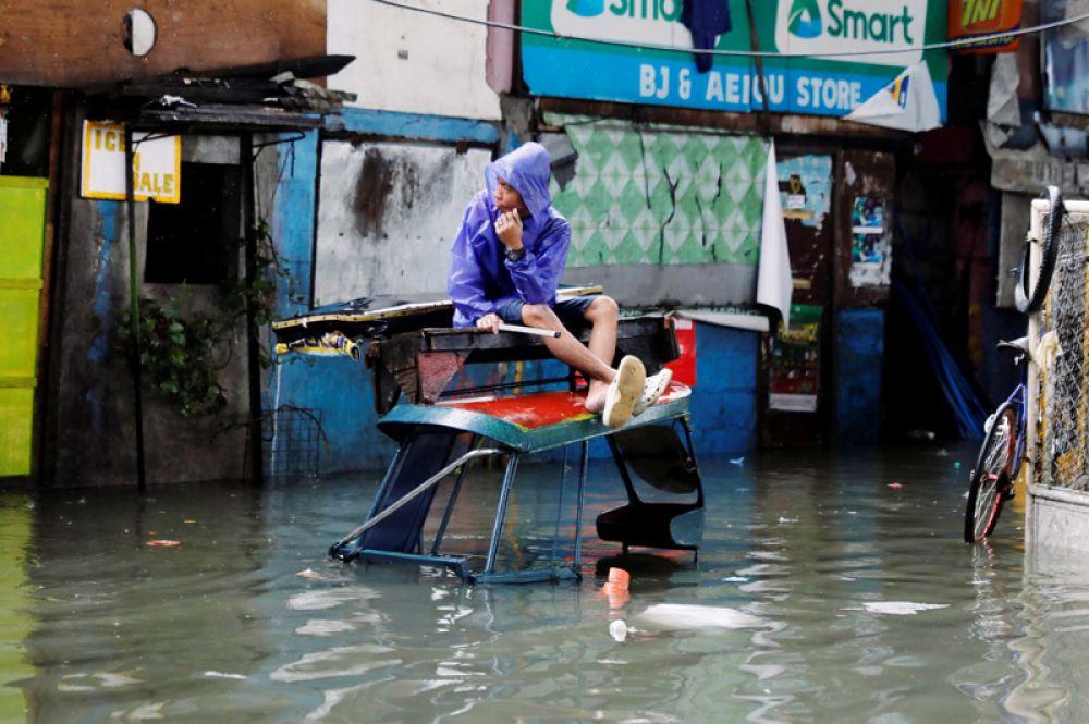 Мужчина на затопленной улице во время муссонных дождей в городе Кесон, Филиппины.