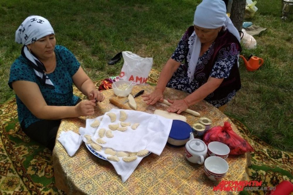 Женщины лепят национальные пироги в картошкой.