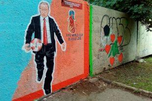 На граффити Президент России, изображённый в костюме, наносит удар по мячу.
