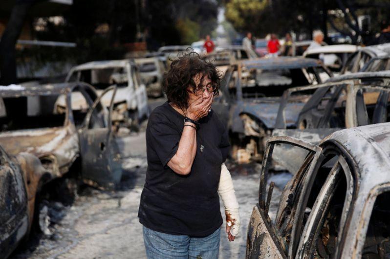 Женщина пытается найти свою собаку после пожара в Мати недалеко от Афин.