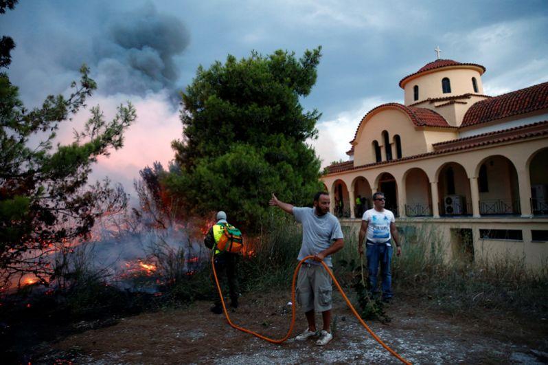 Местные жители принимают участие в тушении пожара рядом с церковью в городе Рафина недалеко от Афин.