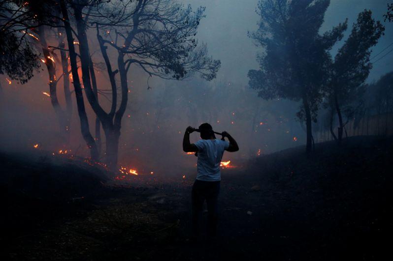 Человек пытается защититься от дыма с помощью собственной одежды в городе Рафина неподалеку от Афин.