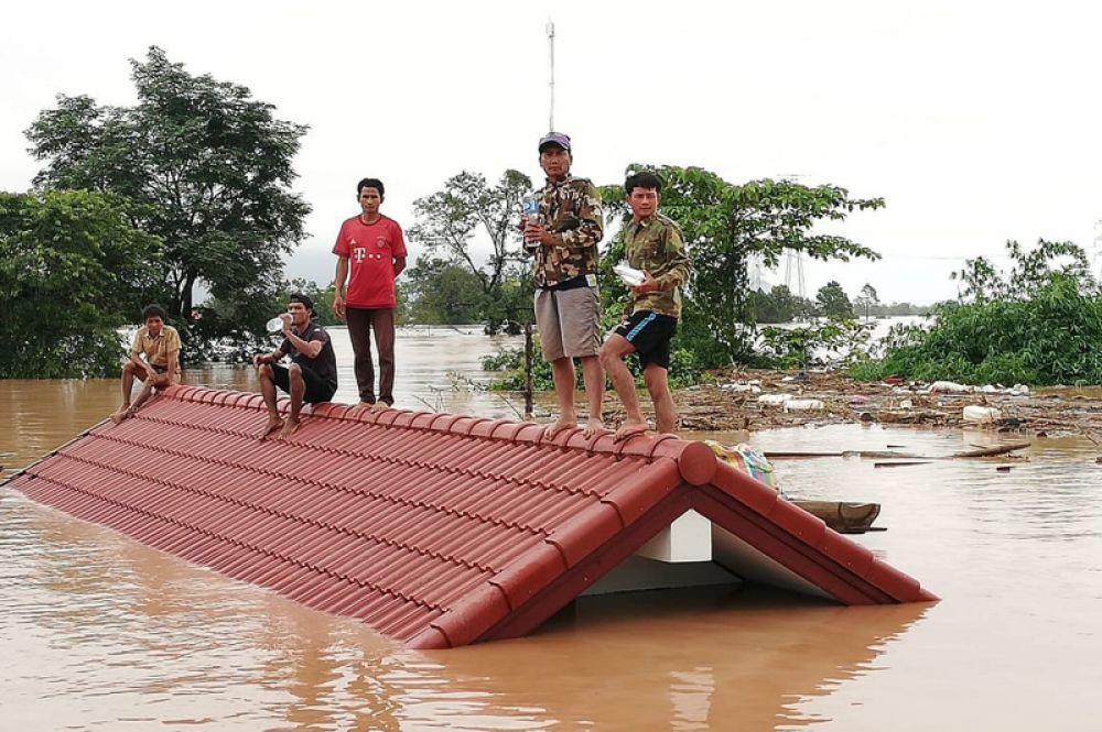 Местные жители на затопленной территории в провинции Аттапы.