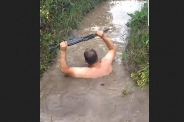 Бойцы передвигаются по затопленным окопам на Донбассе