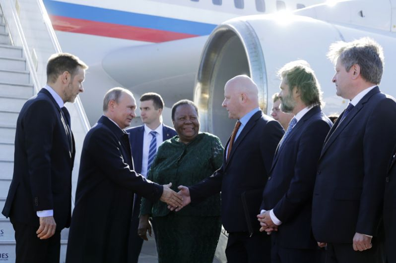 Владимир Путин, прибывший на десятый саммит БРИКС, в аэропорту Йоханнесбурга. Слева - чрезвычайный и полномочный посол РФ в ЮАР Михаил Петраков, третья слева на первом плане - министр высшего образования и профессиональной подготовки ЮАР Наледи Пандор.